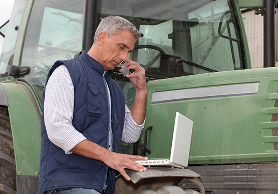 Farmer using a mobile phone and laptop.