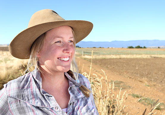 Young female farmer standing next to a field